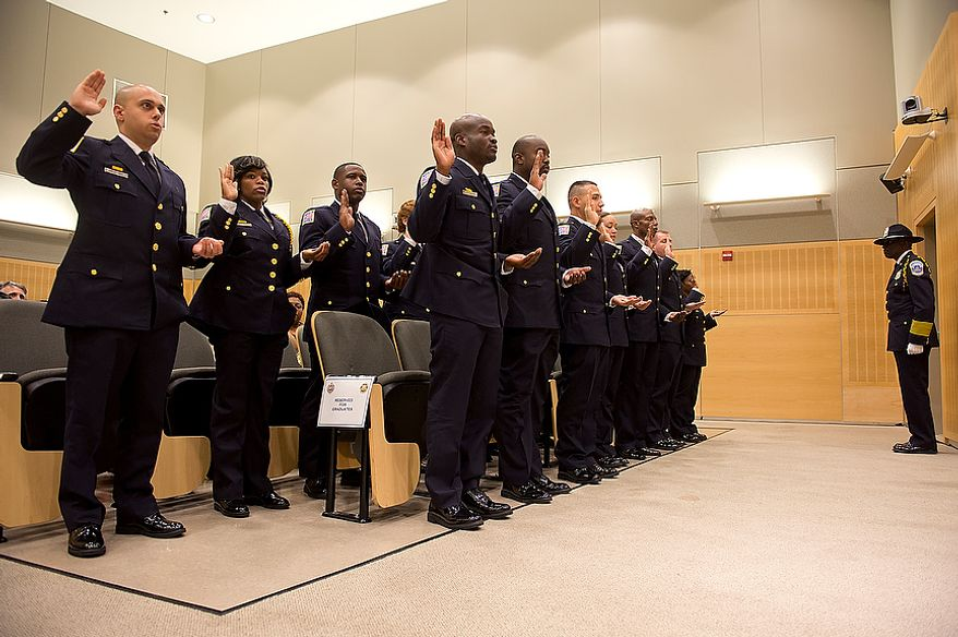 Metropolitan Police Department recruit class 2012-3 hold their badges in their left hands and raise their right hands while being administered the oath of office on Oct. 26, 2012, at the Metropolitan Police Academy in Southwest Washington. (Barbara L. Salisbury/The Washington Times)