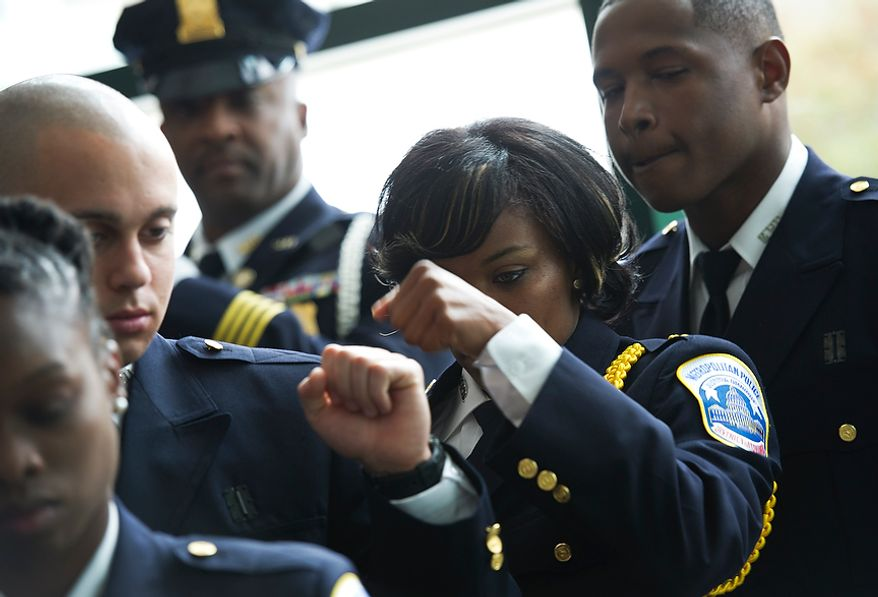 Officer Tiffany Green (right) fist-bumps Officer Anthony Grameri before they process into the auditorium at the Metropolitan Police Academy in Southwest Washington for their graduation on Oct. 26, 2012. Fifteen new officers joined the MPD after seven months of training at the academy. (Barbara L. Salisbury/The Washington Times)