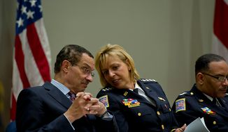 D.C. Mayor Vincent Gray and MPD Chief Cathy Lanier have a private conversation Oct. 26, 2012, during the graduation ceremony for Metropolitan Police Department's recruit class 2012-3. (Barbara L. Salisbury/The Washington Times)