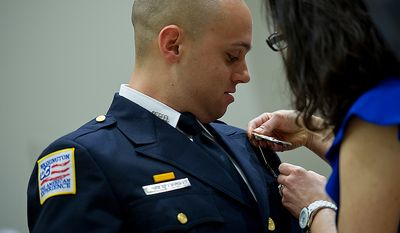 Officer Anthony Grameri gets his badge pinned on by his mother at his graduation ceremony on Oct. 26, 2012. Grameri and 14 others joined the Metropolitan Police Department following seven months of training at the Metropolitan Police Academy in Southwest Washington. (Barbara L. Salisbury/The Washington Times)