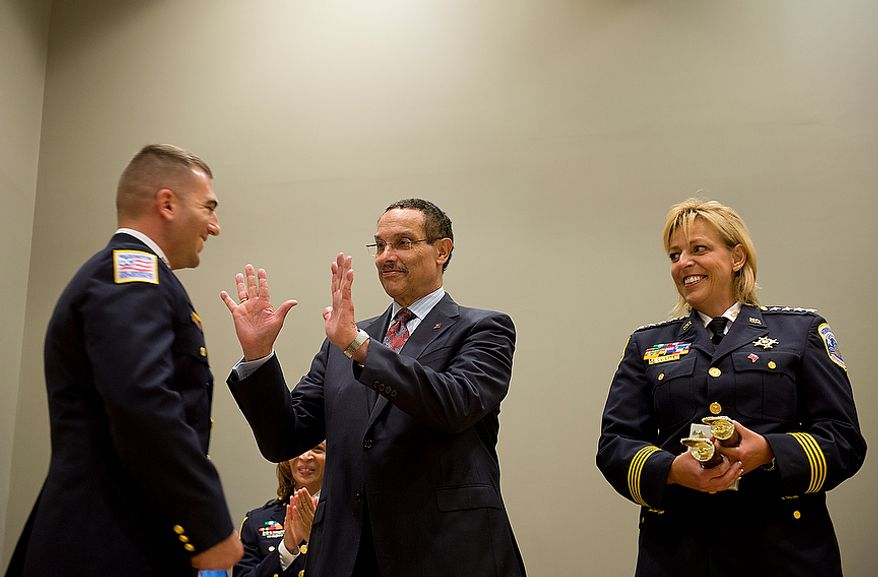 D.C. Mayor Vincent Gray holds up his hands for a double high-five from a new Metropolitan Police Department officer on Oct. 26, 2012, during a graduation ceremony at the Metropolitan Police Academy in Southwest Washington. (Barbara L. Salisbury/The Washington Times)