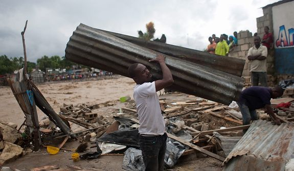 A resident carries a metal sheet, part of a damaged house after heavy rains brought by Hurricane Sandy in Port-au-Prince, Haiti, on Oct. 25,  2012. Sandy was blamed for the death of an elderly man in Jamaica who was crushed by a boulder. Another man and two women died while trying to cross storm-swollen rivers in southwestern Haiti. (Associated Press)