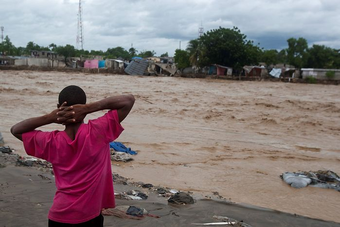 A man watches a river affected by heavy rains brought by Hurricane Sandy in Port-au-Prince, Haiti, on Oct. 25,  2012. Sandy was blamed for the death of an elderly man in Jamaica who was crushed by a boulder. Another man and two women died while trying to cross storm-swollen rivers in southwestern Haiti. (Associated Press)