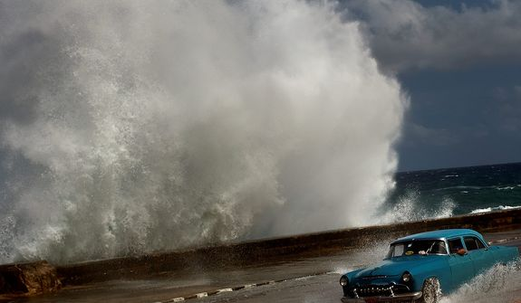 A driver maneuvers his classic American car along a wet road in Havana on Oct. 25, 2012, as a wave crashes against the car. Hurricane Sandy blasted across eastern Cuba as a potent Category 2 storm and headed for the Bahamas after causing at least two deaths in the Caribbean. (Associated Press)