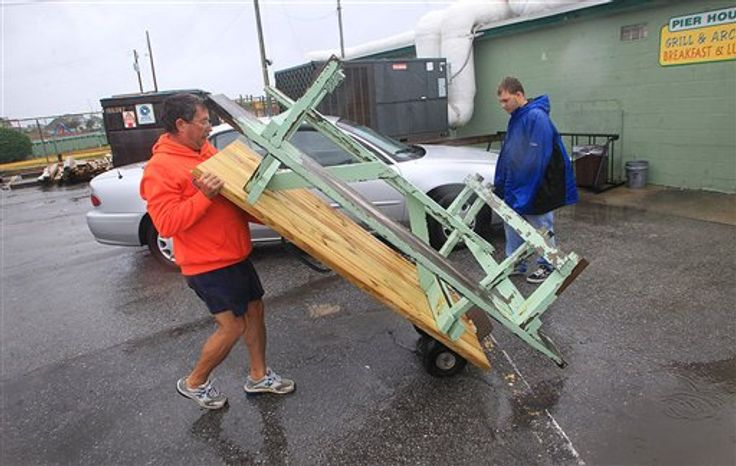 Wayne Bumgarner and his step-son, Bradley Smithson help their friends at the Oceanana Pier in Atlantic Beach by securing the tables from the blowing winds, Saturday, Oct. 27, 2012 in Atlantic Beach, N.C. (AP Photo/The Jacksonville Daily News, Chuck Beckley)