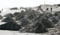 Piles of sand were trucked onto the beach at 2nd Avenue in North Wildwood, N.J., Friday Oct. 26, 2012 as the storm approaches. A year after being walloped by Hurricane Irene, residents rushed to put away boats, harvest crops and sandbag boardwalks Friday as the Eastern Seaboard braced for a rare megastorm that experts said would cause much greater havoc (AP Photo/The Press of Atlantic City, Dale Gerhard)
