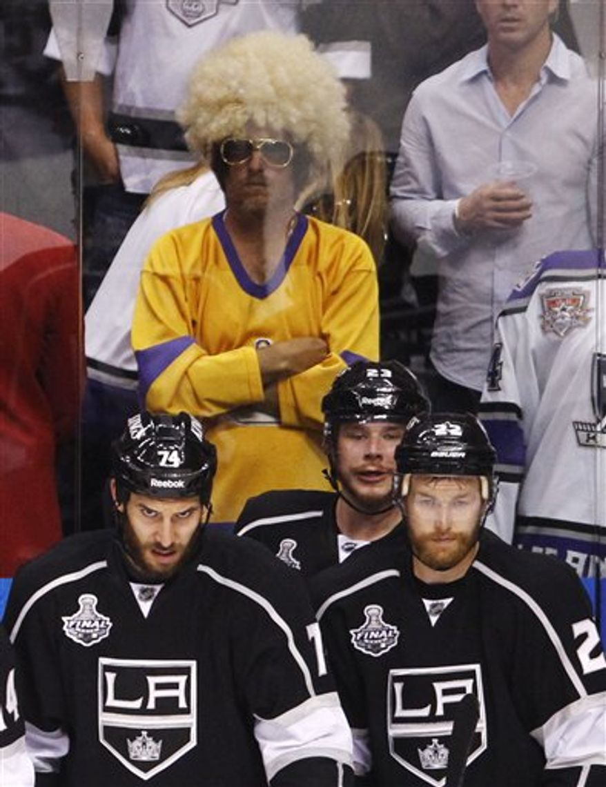 FILE - In this June 6, 2012, file photo, Los Angeles King players, from left, Dwight King, Dustin Brown and Trevor Lewis watch the closing seconds of play against the New Jersey Devils in the third period of Game 4 of NHL hockey's Stanley Cup finals in Los Angeles. The NHL announced Friday, Oct. 26, 2012, that it has canceled all its games through the end of November because of the labor dispute between owners and players. (AP Photo/Jae C. Hong, File)