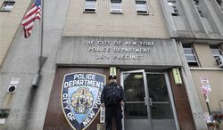 A police officer stands guard outside the New York Police Department's 26th Precinct on Thursday, Oct. 25, 2012. (AP Photo/Mary Altaffer)