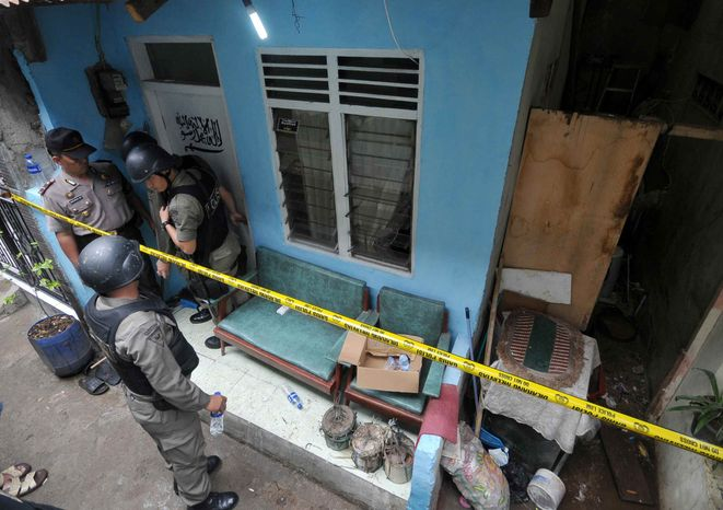 Indonesian police officer stand guard outside the house of a suspected terrorist after a raid in Jakarta, Indonesia, Saturday, Oct. 27, 2012. Indonesian police say they have arrested 11 people suspected of planning a range of terrorist attacks on domestic and foreign targets including the U.S. and Australian embassies. (AP Photo/Jefta)