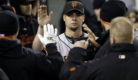 San Francisco Giants starting pitcher Ryan Vogelsong is congratulated in the dugout after leaving the game during the sixth inning of Game 3 of baseball's World Series against the Detroit Tigers Saturday, Oct. 27, 2012, in Detroit. (AP Photo/David J. Phillip)