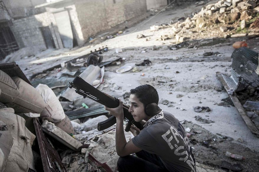 In this Friday, Oct. 26, 2012, photo, a Syrian rebel fighter takes cover as he watches over the enemy position as mortar explosions and gunfire in Aleppo, Syria, on the first day of Eid Al-Adha. (AP Photo/Narciso Contreras)
