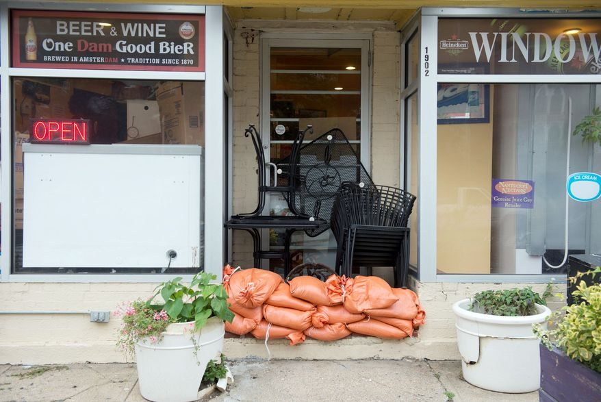 Sandbags sit outside the doorway, and outdoor chairs and tables have been moved into an alcove of a business, along Rhode Island Avenue in the District on Sunday in anticipation of high water levels from Hurricane Sandy. (Barbara L. Salisbury/The Washington Times)