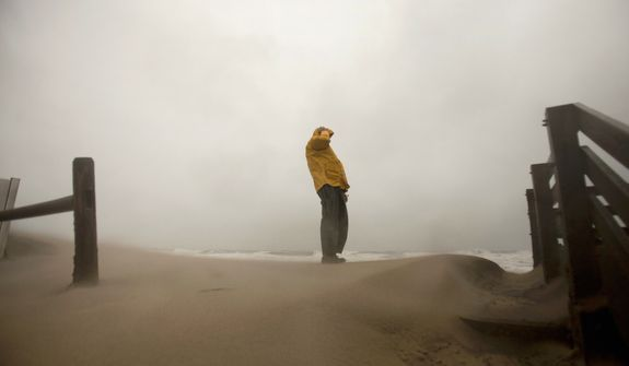 Matt Francis of Virginia Beach holds on to his hat as the wind-driven sand and rain from Hurricane Sandy blow across the beaches of Sandbridge in Virginia Beach on Sunday, Oct. 28, 2012. (L. Todd Spencer/The Virginian-Pilot)