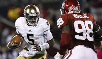Notre Dame quarterback Everett Golson (5) scrambles as Oklahoma defensive end Chuka Ndulue (98) defends during the second quarter of an NCAA college football game in Norman, Okla., Saturday, Oct. 27, 2012. (AP Photo/Alonzo Adams)