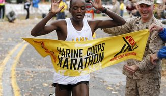 Augustus Maiyo of Colorado Springs, Co. crosses the finish line as he wins the Marine Corps Marathon with a time of 2:20:20 in Washington, on Sunday,  Oct. 28,  2012.More than 30,000 people participated in the Marine Corps Marathon 2012. ( AP Photo/Jose Luis Magana)