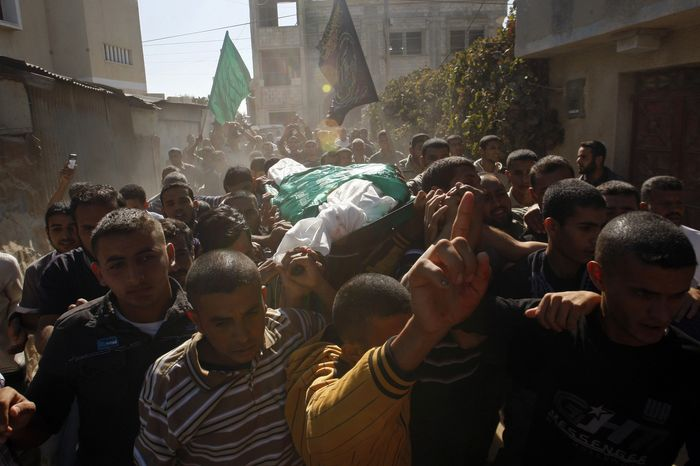 Palestinian mourners carry the body of Hamas militant Suleiman al-Qarra during his funeral in Khan Younis, Gaza Strip, on Sunday, Oct. 28, 2012. A deadly Israeli airstrike and rocket and mortar fire from Gaza on Sunday marred a fragile truce that took hold late last week. (AP Photo/Hatem Moussa)