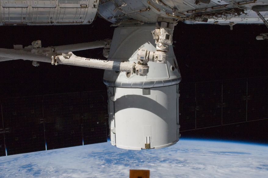 The SpaceX Dragon commercial cargo craft is berthed on the Earth-facing side of the International Space Station's Harmony node on Wednesday, Oct. 10, 2012. (AP Photo/NASA)