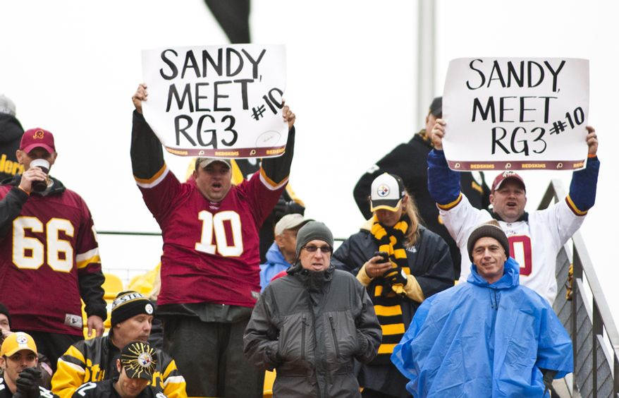 Fans hold up signs before the Pittsburgh Steelers at Heinz Field, Pittsburgh, Pa., Sunday, Oct. 28, 2012. Cooley will be playing his first game of the season against the Steelers today. (Craig Bisacre/The Washington Times)