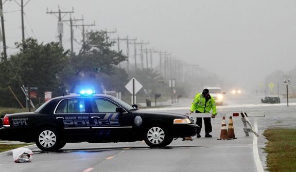 A police officer sets up a road block on South Oregon Inlet Road as water from Hurricane Sandy covers the road in Nags Head, N.C. (AP Photo/Gerry Broome)