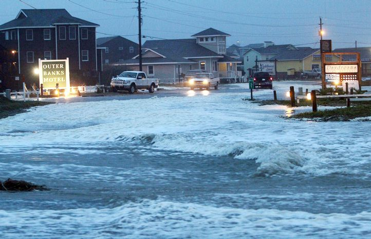 Ocean water rolls over NC 12 at the north end of Buxton, N.C. at dawn on Sunday, Oct. 28, 2012. Waves from offshore Hurricane Sandy are battering Hatteras Island. (AP Photo/The Virginian-Pilot, Steve Earley)