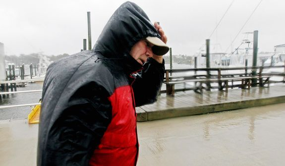 Skip Horney shields himself from the blowing rain after helping secure boats at Broad Creek Marina in Wanchese, N.C., Sunday, Oct. 28, 2012, as Hurricane Sandy moves up the East Coast. (AP Photo/Gerry Broome)