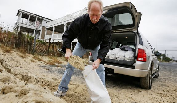 Mike Strobel fills sand bags for his business, Mike's Carpet Connection, as Hurricane Sandy bears down on the East Coast, Sunday, Oct. 28, 2012, in Fenwick Island, Del. (AP Photo/Alex Brandon)