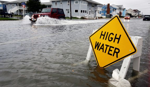 A car goes through the high water as Hurricane Sandy bears down on the East Coast, Sunday, Oct. 28, 2012, in Ocean City, Md.  Governors from North Carolina, where steady rains were whipped by gusting winds Saturday night, to Connecticut declared states of emergency. (AP Photo/Alex Brandon)