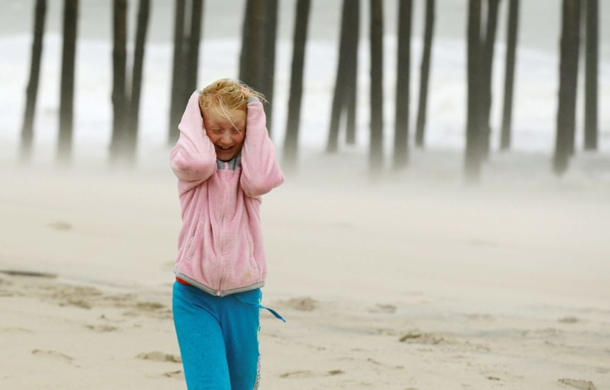 Molly White, 9, from Frankford, Del., covers her head as she is pelted by blowing sand on the beach, as Hurricane Sandy bears down on the East Coast in Ocean City, Md. (AP Photo/Alex Brandon)