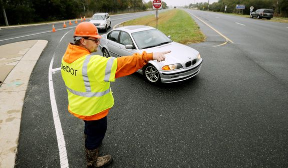 A worker with the Delaware Department of Transportation directs traffic off of Highway 1 at Fred Hudson Road as Hurricane Sandy bears down on the East Coast, Sunday, Oct. 28, 2012, in Bethany Beach, Del. Highway 1 is closed northbound from this point with water over the road according to the Delaware State Police. (AP Photo/Alex Brandon)