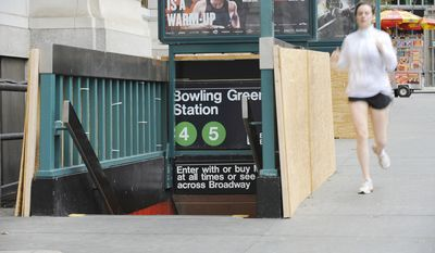 Plywood covers part of the entrance to Bowling Green Station in Battery Park as storm preparation is done in New York. (AP Photo/ Louis Lanzano)