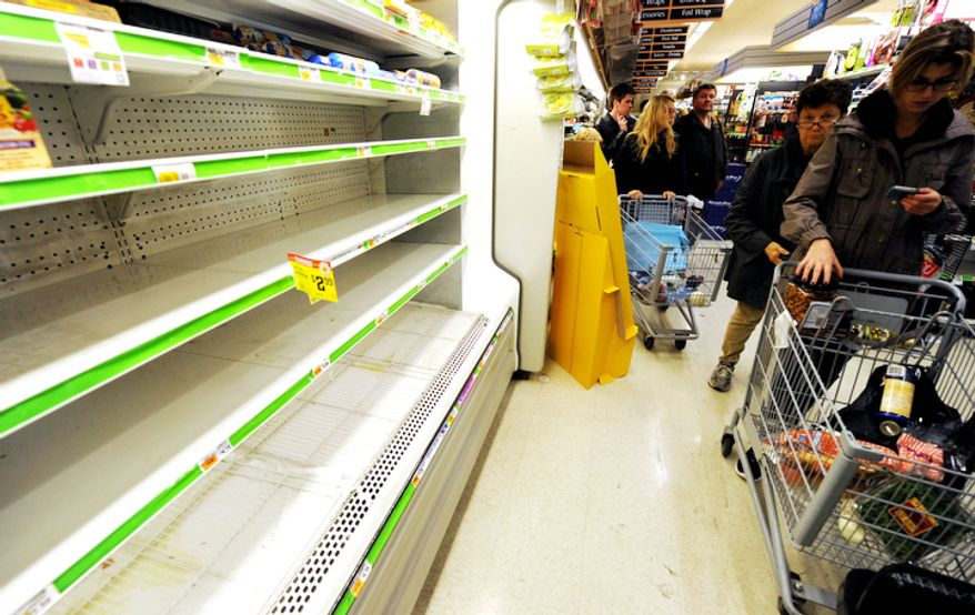 Customers shop for food at a Supermarket in Manhattan.  (AP Photo/ Louis Lanzano)