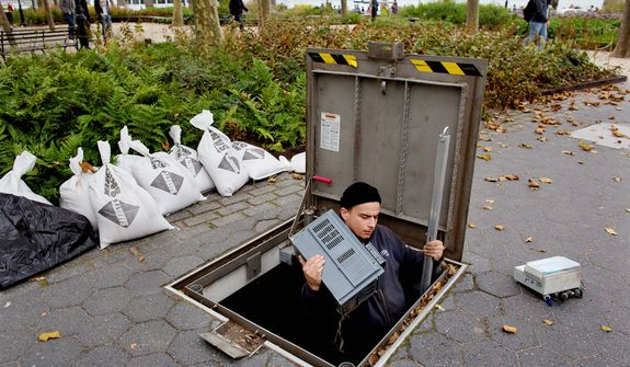 A technician with the Battery Conservancy removes below-ground fountain operation equipment near the water's edge at Battery Park in New York. Areas in the Northeast are preparing for the arrival of Hurricane Sandy and a possible flooding storm surge. (AP Photo/Craig Ruttle)