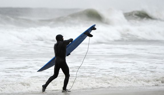 A surfer holds tight to his board against the strong winds and high surf of the Atlantic Ocean before the arrival of Hurricane Sandy on Sunday, Oct., 28, 2012, in Long Beach, N.Y.  (AP Photo/Kathy Kmonicek)