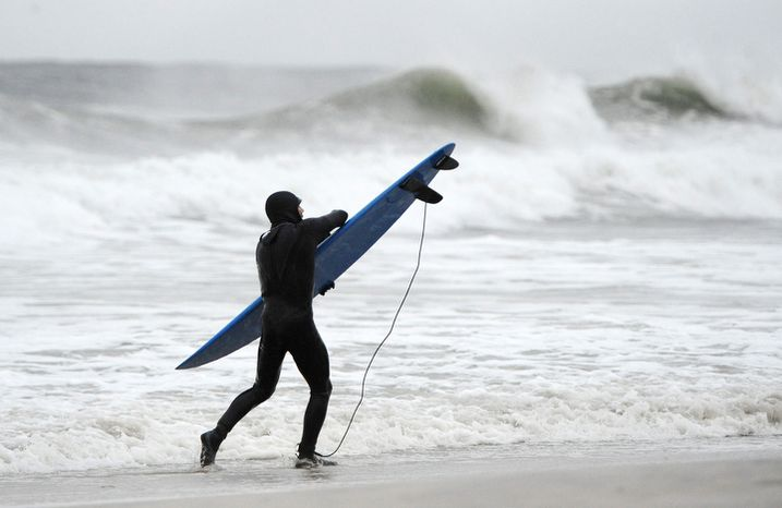 A surfer holds tight to his board against the strong winds and high surf of the Atlantic Ocean before the arrival of Hurricane Sandy on Sunday, Oct., 28, 2012,