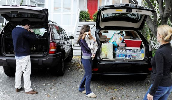 The Flaven family pack up their cars before evacuating the area in Fairfield, Conn., Sunday, Oct. 28, 2012. Mandatory evacuations have been ordered for Sunday in parts of Bridgeport, Fairfield, East Haven, Old Lyme, Old Saybrook and Branford. Voluntary evacuations are being urged in parts of Westport and New London. (AP Photo/Jessica Hill)