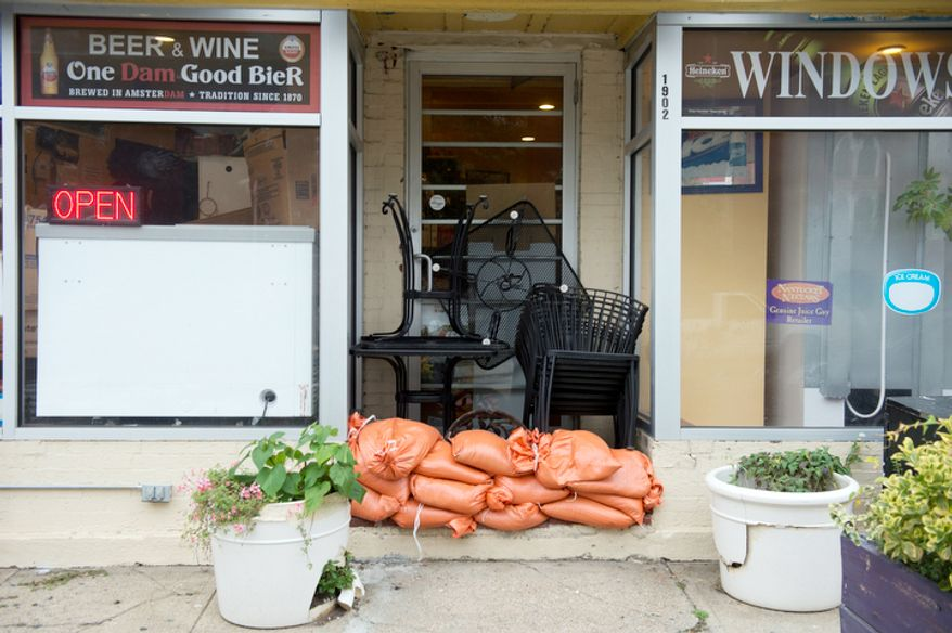 Sandbags sit outside the doorway and outdoor chairs and tables have been moved into an alcove of a business along Rhode Island Avenue in Washington, D.C. on Sunday, Oct. 28, 2012 in anticipation of high water levels from Sandy, the super storm that is expected to hit the area Sunday night or early Monday morning. (Barbara L. Salisbury/The Washington Times)