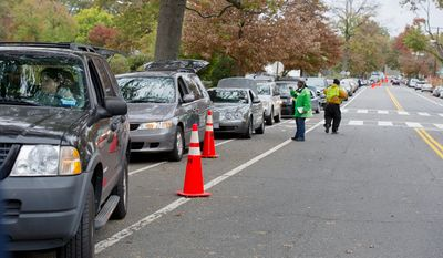 A long line of cars waits outside of Coolidge High School in Washington, D.C. to pick up sandbags from the Department of Public Works on Sunday, Oct. 28, 2012 in anticipation of high water levels from large amounts of rain due to Hurricane Sandy.  (Barbara L. Salisbury/The Washington Times)