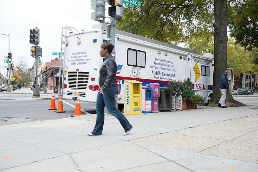 "A woman walks past the District of Columbia Homeland Security and Emergency Management Agency Mobile Command Unit on the corner of Rhode Island Avenue and First Street N.W. on Sunday, Oct. 28, 2012. This unit has been positioned in the Bloomingdale neighborhood in anticipation of Sandy, the so-called ""Frankenstorm"" that is due to hit the D.C. area by Monday morning. (Barbara L. Salisbury/The Washington Times)"