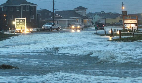 Ocean water rolls over Route 12 at the north end of Buxton, N.C., at dawn on Sunday, Oct. 28, 2012, as waves from Hurricane Sandy battered Hatteras Island. (AP Photo/The Virginian-Pilot, Steve Earley)