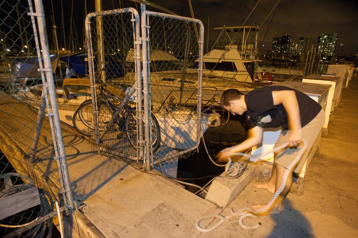 Tad Kanski of Newport Beach, Calif., unties his family's sailboat, moored at the Ala Wai Harbor in Honolulu, after learning of a tsunami warning on Saturday, Oct. 27, 2012. (AP Photo/Eugene Tanner)
