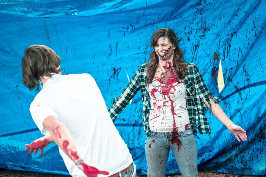 James Howard, splashes blood over a volunteer as the final stage to becoming a zombie at Run for Your Lives, a zombie infested 5k obstacle course run. Runners had to avoid zombie and overcome obstacles in order to complete the race. (Andrew S. Geraci/The Washington Times)