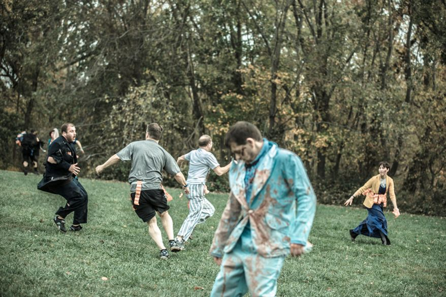 Runners try to avoid loosing their flags to herds of zombies as they make their way towards the finish line at, Run for Your Lives, a zombie infested 5k obstacle course run, in Darlington, MD., Saturday, October 27, 2012. Participants tried their best to avoid being chased and grabbed as they ran the 5k long course. Runners who completed the course without loosing all of their flags were rewarded with a medal of survival.  (Andrew S. Geraci/The Washington Times)