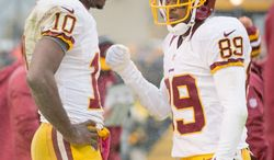 Quarterback Robert Griffin III (left) talks with receiver Santana Moss, who with five touchdowns is on pace to match his career-best of 10 set with the New York Jets in 2003. However, the Redskins would like to see more from Leonard Hankerson and Aldrick Robinson. (Andrew Harnik/The Washington Times)