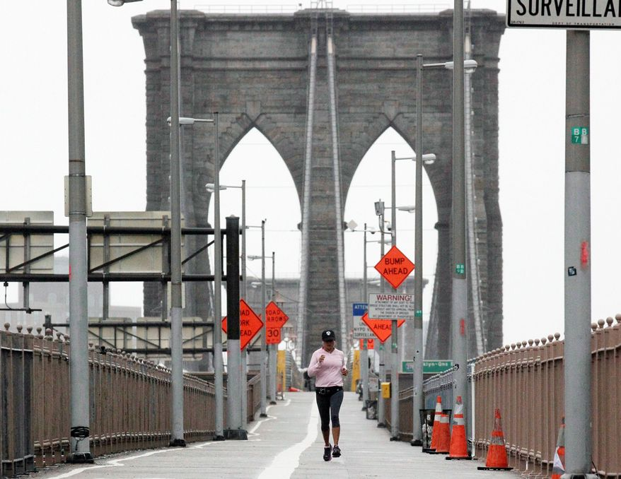 ** In this Oct. 29, 2012, file photo, a woman jogs across the Brooklyn Bridge in New York City. Many city residents were defiant as Hurricane Sandy moved toward the region, going about their daily routines in an attempt to maintain normalcy despite the worsening conditions. (Associated Press)