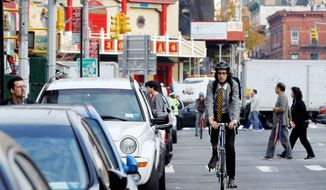 Dan Rollman rides his bike on Canal Street in New York City. The CEO of RecordSetter.com is also a co-founder of Sabbath Manifeso, a movement that encourages people to unplug one day a week to make time for solitude or for relaxation with family and friends away from computers and cellphones. (Associated Press)