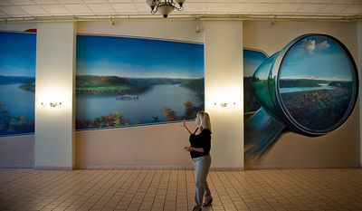 Debi Froehlich looks at a large mural of the untouched original landscape of the town of Steubenville, Ohio, Friday, October 26, 2012. Debi, who owns Froehlich Classic Corner restaurant with her husband Greg, also owns the much larger building the restaurant occupies which was at one point the electric company for the town. This room used to be a Jaguar automobile museum and is now used as space for parties and weddings. Once a productive steel town, Steubenville, Ohio's population has contracted faster than anywhere else in the country between 1980 and 2000 as their steel plants shut down. The area has seen a drop in unemployment in recent years due in part to the prospects of natural gas but the city still has a long way to go with unemployment figures higher then the the rest of the state and the country. (Andrew Harnik/The Washington Times)