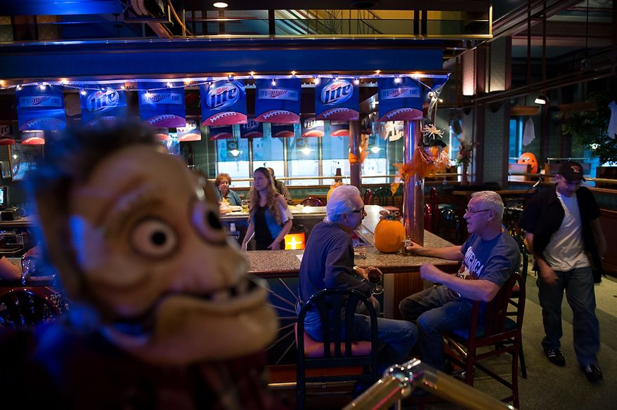 """Steve Gagliardi of Steubenville, Ohio, second from right, and Paul Grant, third from right, talk together at the bar at Froehlich's Classic Corner restaurant, Steubenville, Ohio, Friday, October 26, 2012. Of the election Gagliardi says, """"I'm a Romney supporter. I've been a banker all of my life and the debt of this nation will cripple us."""" Once a productive steel town, Steubenville, Ohio's population has contracted faster than anywhere else in the country between 1980 and 2000 as their steel plants shut down. The area has seen a drop in unemployment in recent years due in part to the prospects of natural gas but the city still has a long way to go with unemployment figures higher then the the rest of the state and the country. (Andrew Harnik/The Washington Times)"""