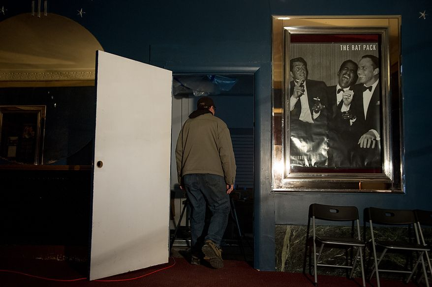 Scott Dressel who has put most of his retirement savings into buying and restoring homes in Steubenville, Ohio, walks past an old poster of Dean Martin, who's hometown was Steubenville, along with Sammy Davis Jr. and Frank Sinatra, in the front lobby of the old Grand Theatre  with citizens have partnered together to buy and renovate to help spur economic development, Steubenville, Ohio, Saturday, October 27, 2012. Once a productive steel town, Steubenville, Ohio's population has contracted faster than anywhere else in the country between 1980 and 2000 as their steel plants shut down. The area has seen a drop in unemployment in recent years due in part to the prospects of natural gas but the city still has a long way to go with unemployment figures higher then the the rest of the state and the country. (Andrew Harnik/The Washington Times)