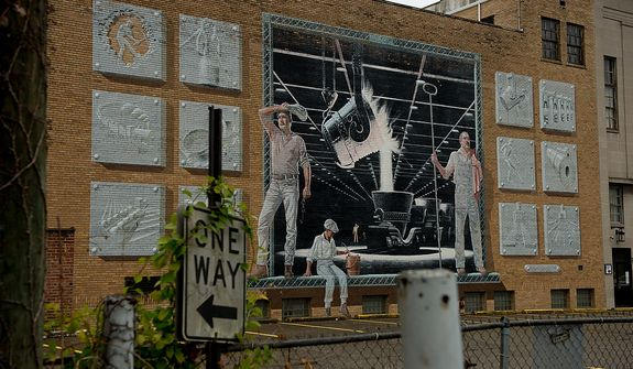 A large mural painted in homage to the steel workers and the steel mills for which the city of Steubenville's main source of jobs came from, is visible in downtown, Steubenville, Ohio, Saturday, October 27, 2012. Once a productive steel town, Steubenville, Ohio's population has contracted faster than anywhere else in the country between 1980 and 2000 as their steel plants shut down. The area has seen a drop in unemployment in recent years due in part to the prospects of natural gas but the city still has a long way to go with unemployment figures higher then the the rest of the state and the country. (Andrew Harnik/The Washington Times)