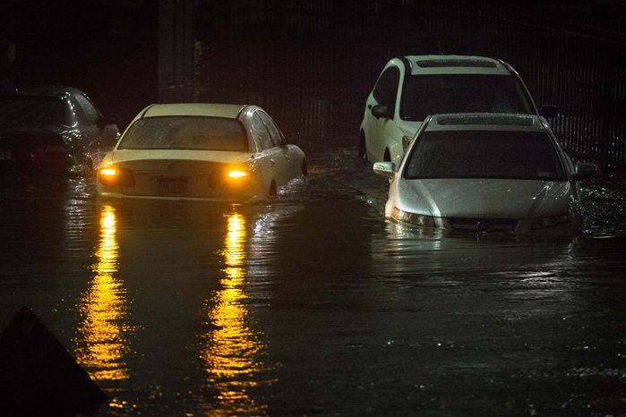 Vehicles are submerged during a storm surge near the Brooklyn Battery Tunnel, Monday, Oct. 29, 2012, in New York. Superstorm Sandy zeroed in on New York's waterfront with fierce rain and winds that shuttered most of the nation's largest city Monday, darkened the financial district and left a huge crane hanging off a luxury high-rise. (AP Photo/John Minchillo)